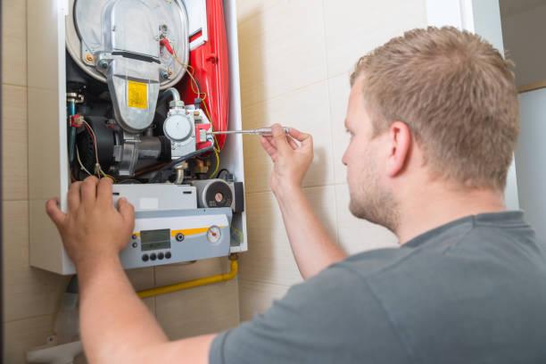 Plombier chauffagiste qui réalise la maintenance annuelle d'une chaudière gaz à condensation